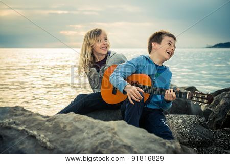 Cute children having a lot of fun with guitar by the sea