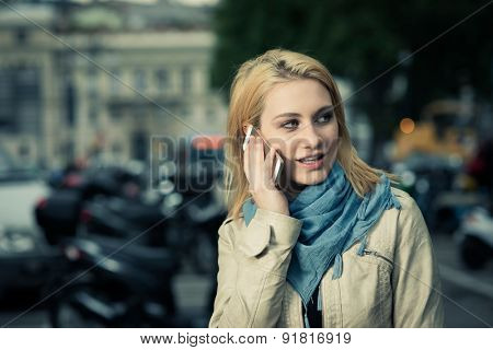 Girl on the phone, her scooter on the background