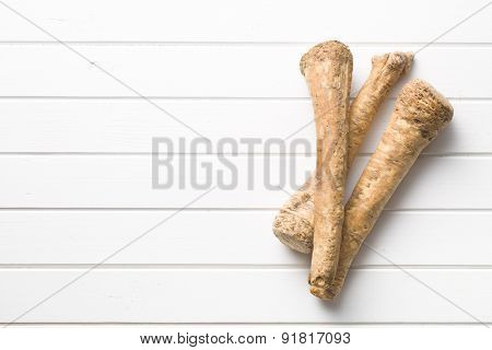 fresh horseradish root on kitchen table