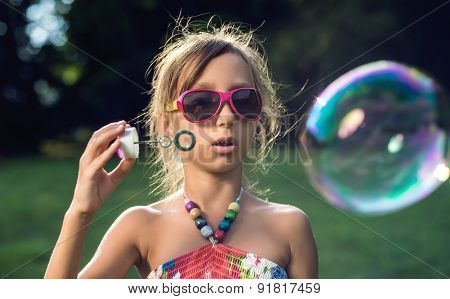 Cute little girl is blowing a soap bubbles on the green grass
