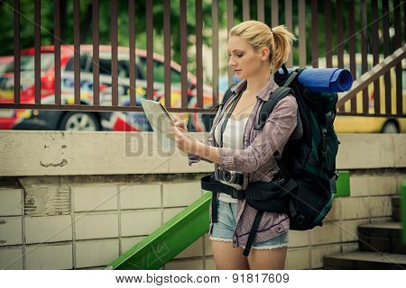Young female backpacker using map in the city