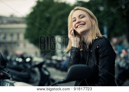 Happy girl speaking on the phone while sitting on her scooter