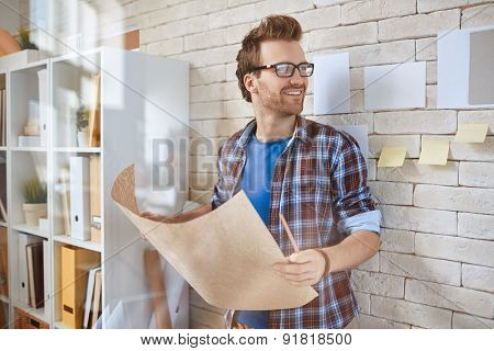 Happy young businessman with blueprint standing by the wall