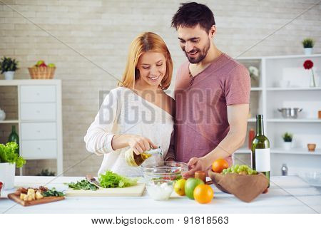 Pretty woman dripping olive oil into salad with her husband near by
