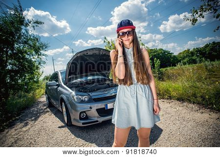 Young woman near broken car speaking by phone needs assistance