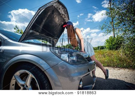young brunette girl near  broken car with open hood