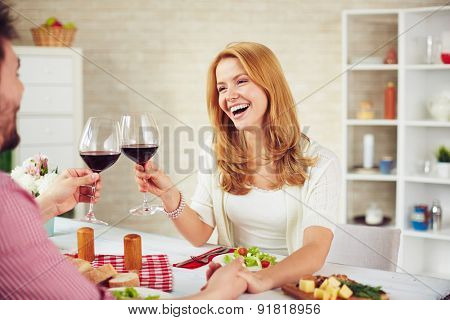 Happy young couple laughing while making toast by dinner table