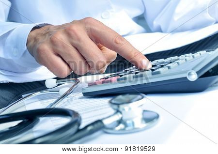 closeup of a young caucasian healthcare professional wearing a white coat calculates on an electronic calculator