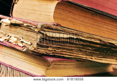 closeup of a pile of worn-out old books on a rustic wooden table
