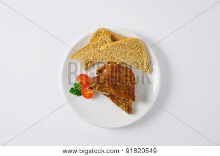 two slices of roasted pork meat with toast bread on white plate