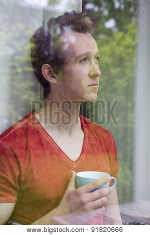 Young Blond Man Looking Out Of Window