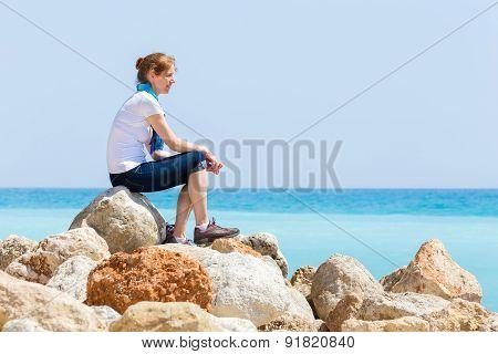 Woman sitting on rocks with blue sea horizon