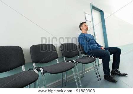 Man Sitting On Chair In Hospital