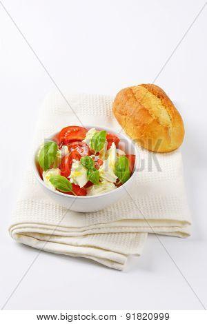 bowl of caprese salad and fresh bun