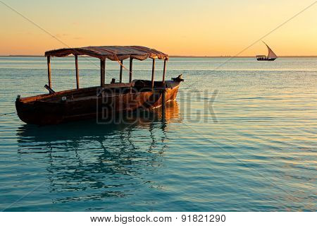 Wooden boat on water at sunset, Zanzibar island