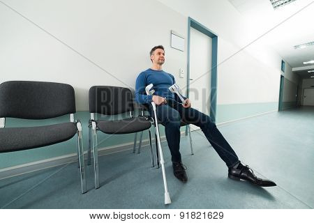 Man With Crutches Sitting On Chair