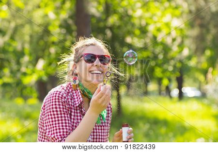 Smiling Beautiful Brunette Girl In Glasses Blowing Soap Bubbles Outdoor