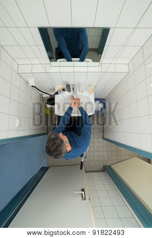 Disabled Man In Bathroom Washing Hands