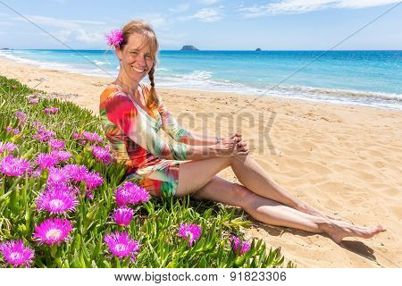 Woman with pink flowers on sandy beach with blue sea