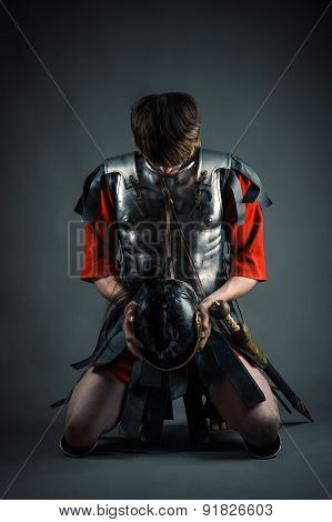 man kneeling with a helmet in hands