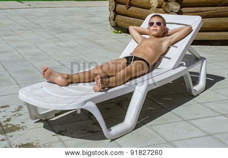 young boy taking a break from swimming and resting on a chaise lounge