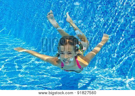 Happy child swims in pool underwater, active kid swimming, playing and having fun