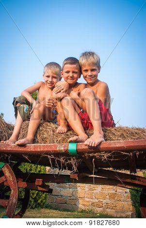 boys sitting on a hay bale on sky background