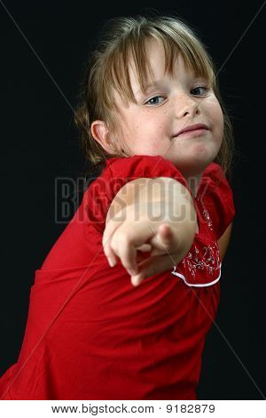 Small girl pointing her finger at you on black