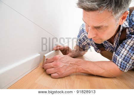 Carpenter Applying Skirting On Wall