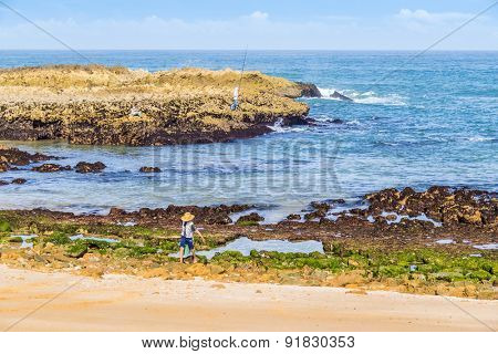 OUALIDIA, MOROCCO, APRIL 6, 2015:  Boy-fisherman carries bucket with freshly caught seafood