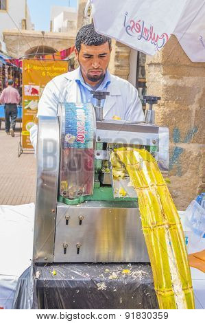 AS-SAWIRA, MOROCCO, APRIL 7, 2015:  seller of sugar cane juice squeezes it for selling