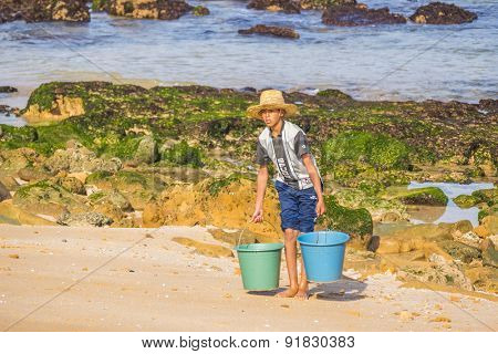 OUALIDIA, MOROCCO, APRIL 6, 2015: Boy-fisherman carries buckets with freshly caught seafood