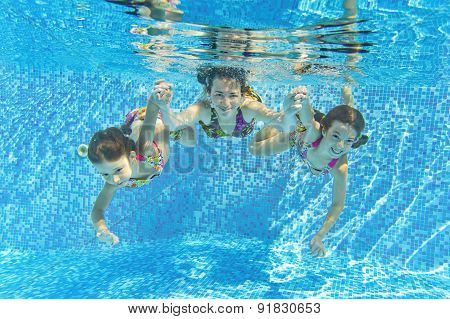 Happy smiling family underwater in swimming pool. Mother and children swim and having fun