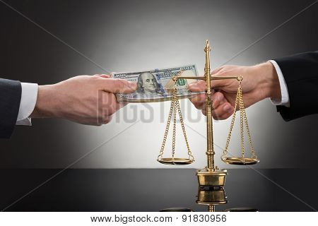 Businessman Taking Bribe In Front Of Justice Scale