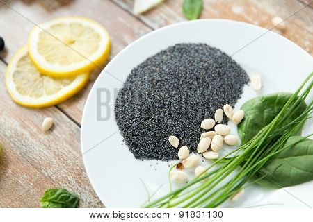 healthy eating, vegetarian super food, culinary and diet concept - close up of peeled peanuts, greens and poppy or chia seeds