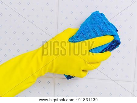 the tiles of a bathroom is cleaned with latex gloves.