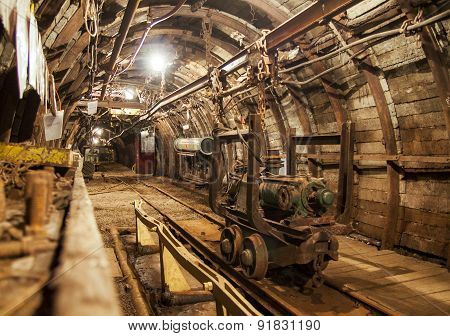 Interior of underground mine passage with rails, light and carriage - mining industry