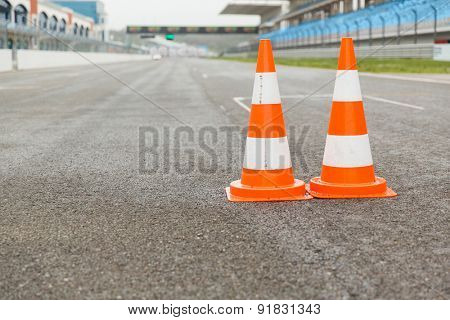 racing, motosports, extreme and motoring concept - traffic cones on speedway of stadium