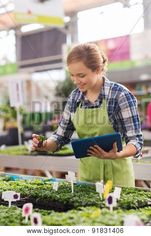 people, gardening, technology and profession concept - happy woman or gardener with tablet pc computer and seedling in greenhouse