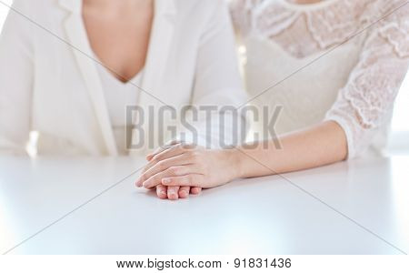 people, homosexuality, same-sex marriage and love concept - close up of happy married lesbian couple hands