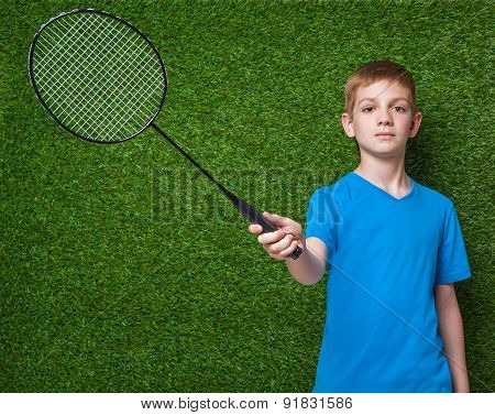 Boy holding badminton racket over green grass