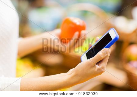 sale, shopping, consumerism and people concept - close up of young woman hands with smartphone and persimmon in market