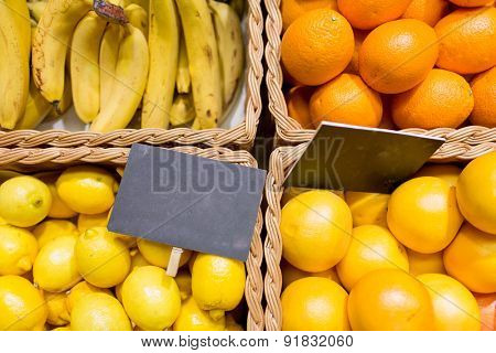 sale, shopping, vitamin c and eco food concept - ripe fruits in baskets with nameplates at grocery market