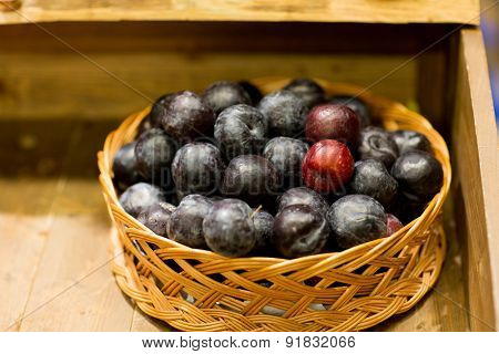sale, farming, agriculture and eco food concept - ripe plums in basket at farm or grocery market