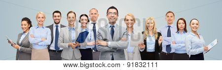 business, people, corporate, teamwork and office concept - group of happy businesspeople over blue b
