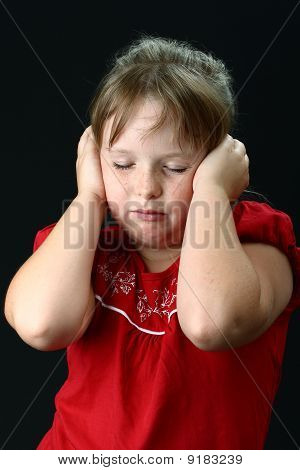 Small girl holding her ears with her hands so that she can't listen