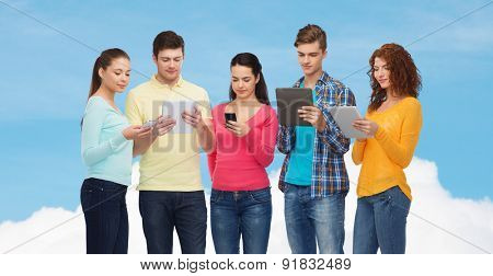 friendship, technolpgy and people concept - group of smiling teenagers with smartphones and tablet pc computers over blue sky with white cloud background