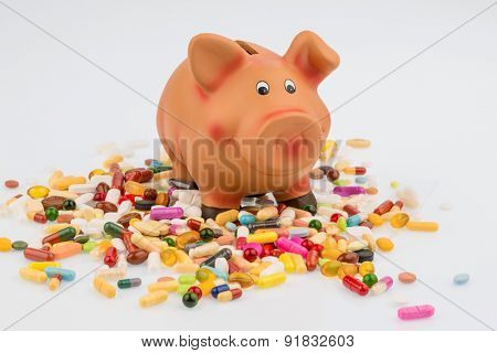 tablets lying next to a piggy bank. symbol photo for costs in medicine and pharmaceutical industry