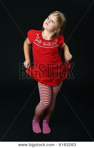 Small girl dancing in red casual clothes on black