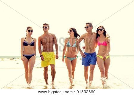 friendship, sea, summer vacation, holidays and people concept - group of smiling friends wearing swimwear and sunglasses walking on beach